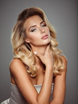 Фотография красивой молодой блондинки с вьющимися волосами. крупным планом привлекательное чувственное лицо белой женщины с длинными волосами. дымчатый макияж глаз.