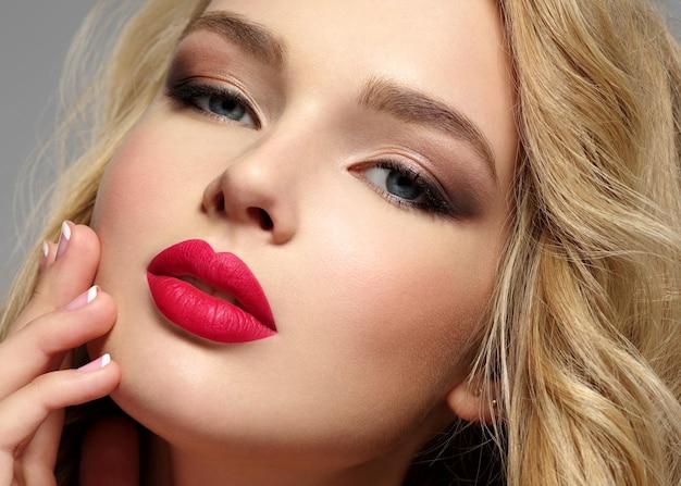Фотография красивой молодой блондинки с сексуальными красными губами. крупным планом привлекательное чувственное лицо белой женщины с длинными вьющимися волосами.