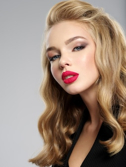 セクシーな赤い唇を持つ美しい若いブロンドの女の子の写真。長い髪の白人女性のクローズアップ魅力的な官能的な顔。スモーキーアイメイク
