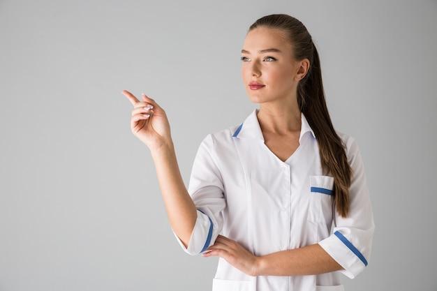 Фото доктора косметолога красивой молодой женщины изолированного над серой указывать стены.