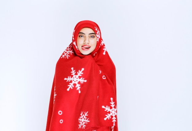 흰 벽에 부드러운 담요로 싸인 아름다운 젊은 여성의 사진.