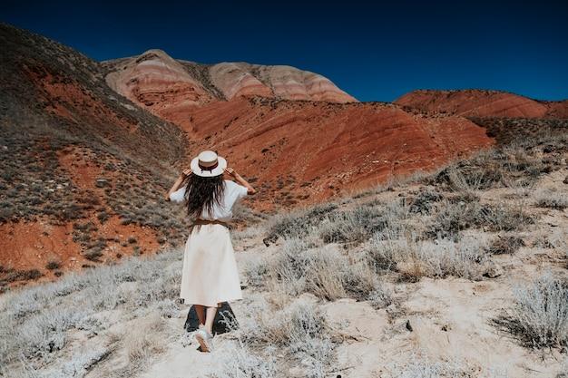 Фотография брюнетки в шляпе в горах со спины.