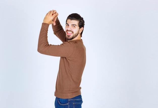 Фото модели человека брюнет стоя задней и показывая сердце руками. фото высокого качества