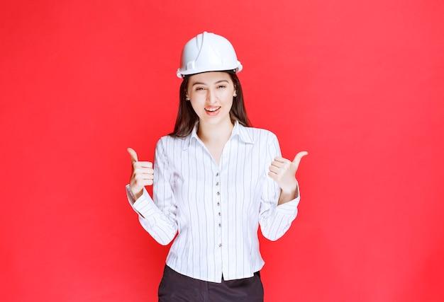 Фото деловой женщины в защитной шляпе показывает палец вверх.