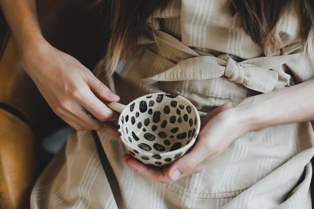 Фото керамической чашки в женских руках крупным планом