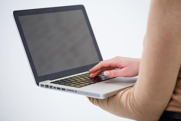 Фотография очаровательной женщины, держащей ноутбук и печатающей по делу