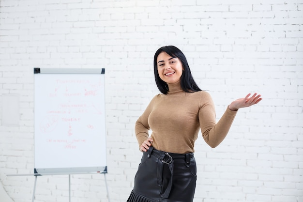 笑顔で魅力的な女性の写真。マーカーで黒板の近くに立っている