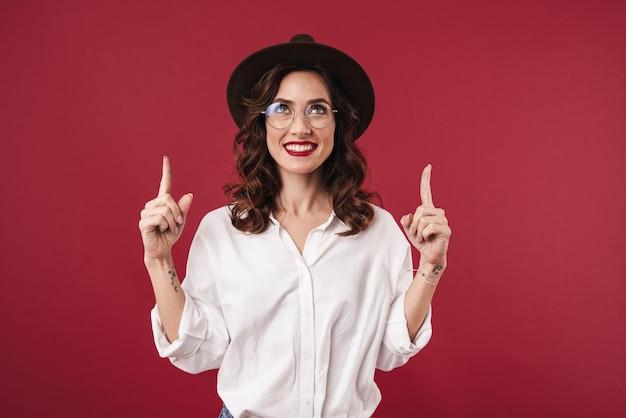 赤い壁を指して孤立してポーズをとって陽気な若い美しい女性の写真。