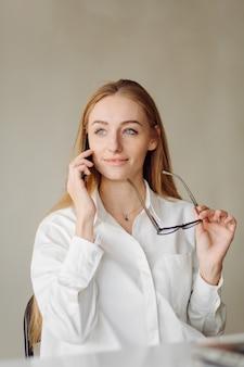 屋内のオフィスで陽気な若い金髪のビジネスウーマンの写真は、ラップトップと携帯電話で動作します。 無料写真