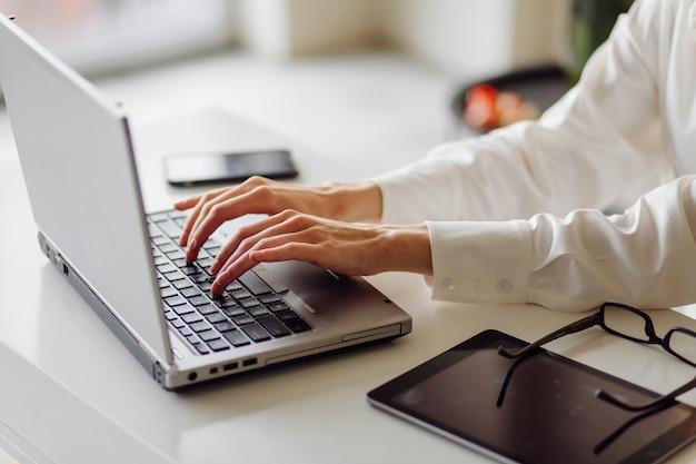 屋内のオフィスで陽気な若い金髪のビジネスウーマンの写真は、ラップトップと携帯電話で動作します。