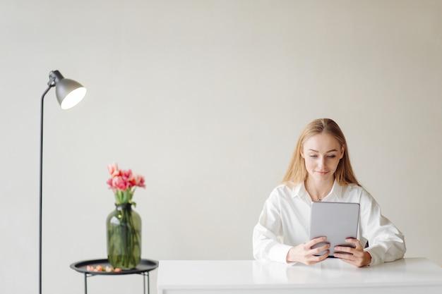 Фотография жизнерадостной молодой блондинки бизнес-леди в офисе в помещении работает с ноутбуком и мобильным телефоном.