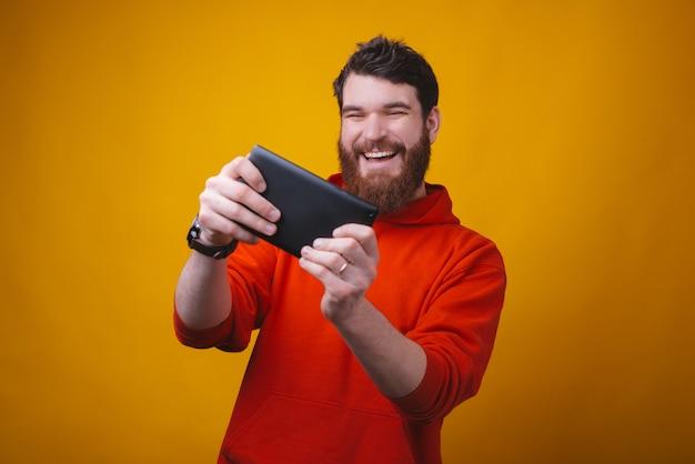 陽気な若い男の写真は、黄色のスペースで彼のタブレットでゲームをプレイすることに興奮しています。