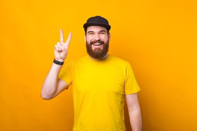 쾌활한 젊은 남자의 사진은 카메라에 미소 평화 기호를 보이고있다