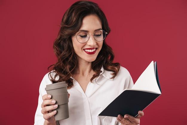 ノートブックを保持している赤い壁に分離されたコーヒーを飲むグラスで陽気な前向きな楽観的な若い女性の写真。