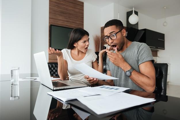 書類を見ながら自宅で家計簿について話し合っている混乱した若いカップルの写真。
