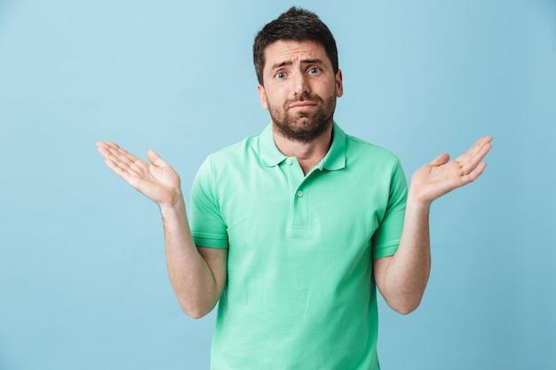 Фото сбитого с толку молодого красивого бородатого мужчины, позирующего изолированно над синей стеной.