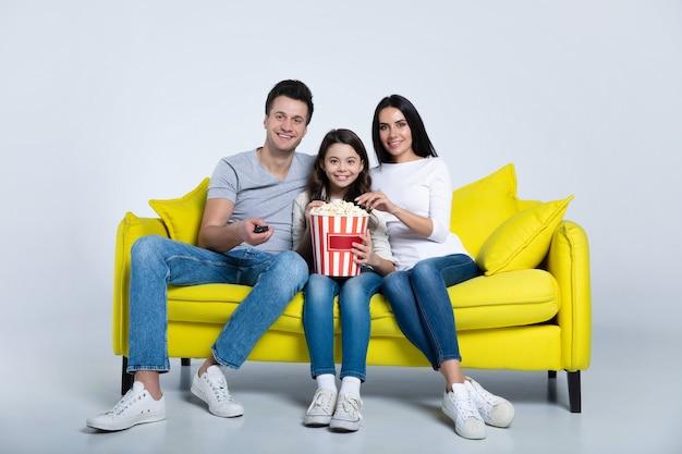 Фотография симпатичного ребенка и ее родителей, которые вместе едят попкорн во время просмотра телешоу на диване.