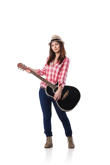 Фотография милой молодой женщины в клетчатой рубашке и шляпе, играющей на гитаре. снято на белом фоне.