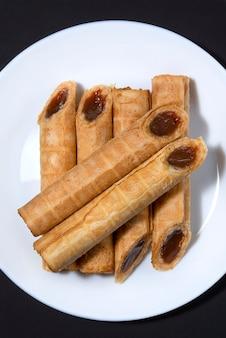 Фото блюда с домашними вафельными трубочками с вареной сгущенкой и орехами на белой тарелке