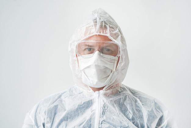 マスクとオーバーオールの医者の写真。前方停止ウイルスを手で。 2019-ncov。孤立した背景の男。
