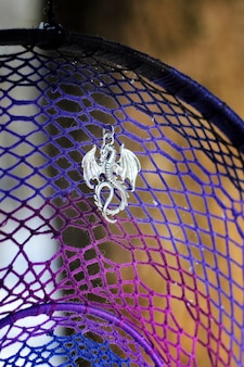 Фото ловца снов, сделанное своими руками, с использованием ниток, бус и перьев петуха.