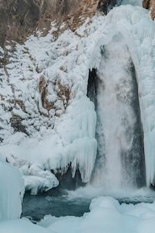 겨울에 산에서 얼어 붙은 폭포의 사진. 러시아, 북 코카서스 산맥.