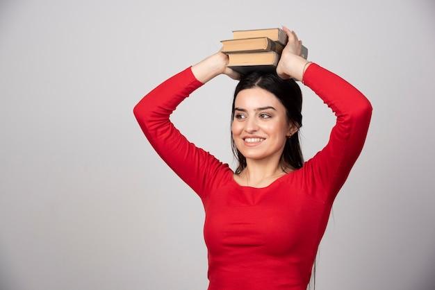 本を頭上に持っている面白い女性の写真。