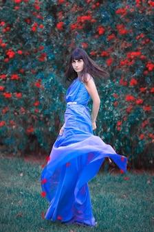 長くエレガントな青いドレスを着た女の子の写真。赤い花びらが落ちる。