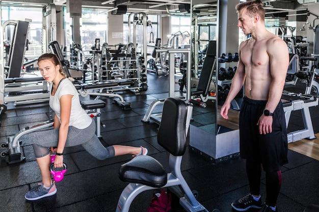 На фото девушка в белой футболке и серых леггинсах делает выпады с гантелями под присмотром фитнес-инструктора.