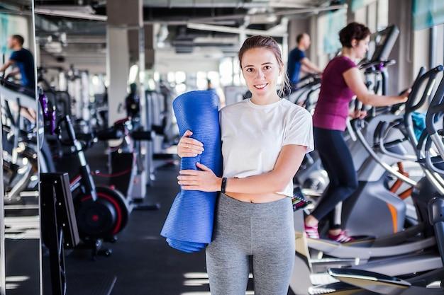 Фотография девушки с гимнастическим ковриком в руках позирует на фоне спортзала. улыбается и смотрит в камеру