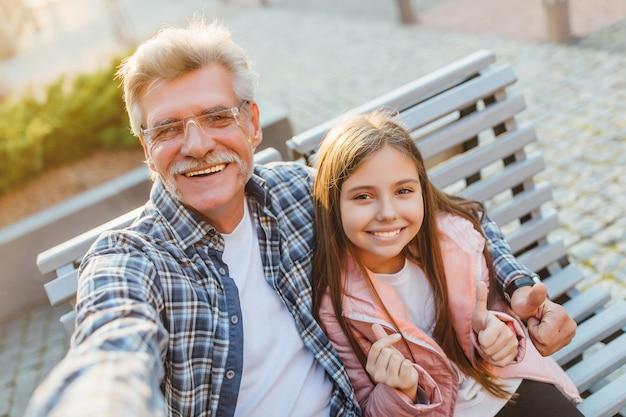 ベンチに座って自分撮りをする祖父と孫娘の写真