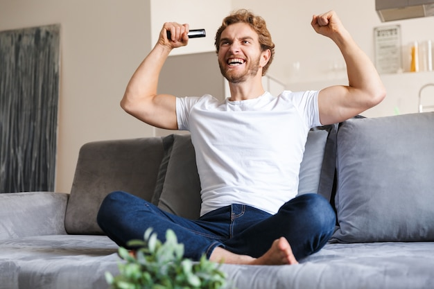 Фотография красивого эмоционального молодого человека на диване у себя дома, держащего телевизор с дистанционным управлением, делает жест победителя.