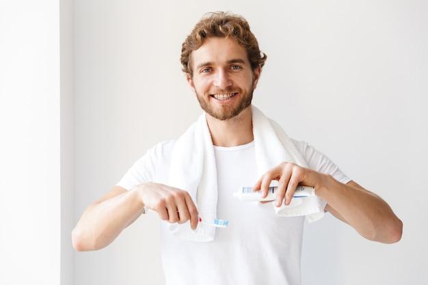 Фото красивого счастливого молодого человека в ванной комнате дома, чистящего его зубы.