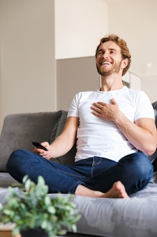 Фотография красивого счастливого молодого человека на диване у себя дома, держащего телевизор с дистанционным управлением.