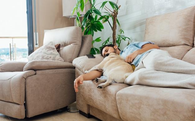 彼の犬と一緒にソファで寝ているハンサムなヒスパニック系男性の写真