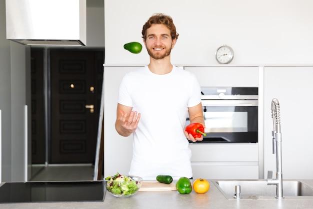家庭で野菜を調理するキッチンでハンサムな若い男の写真はサラダを作ります。