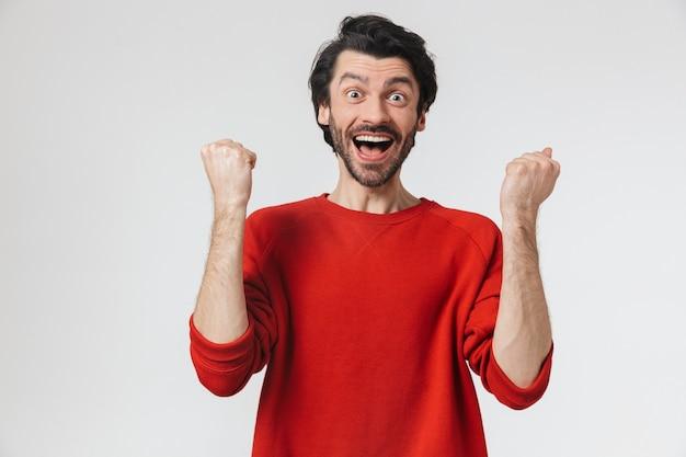 Фотография красивого молодого шокированного человека, позирующего над белой стеной, делает жест победителя.