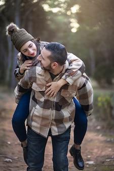 Фотография счастливой пары, наслаждающейся зимним днем на природе