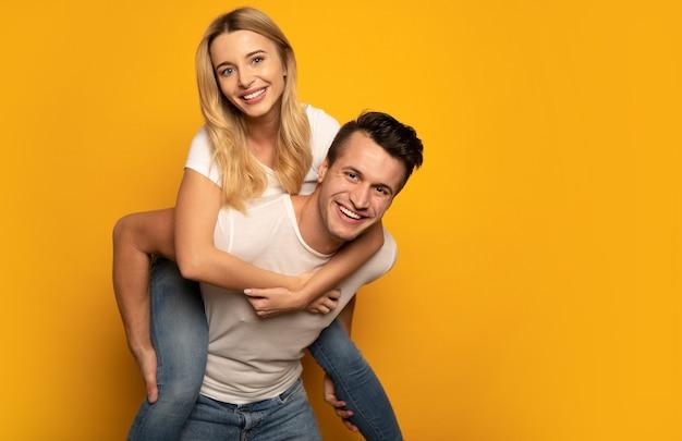 Фотография счастливого человека, который катает свою улыбающуюся подругу на спине, смеясь от радости.