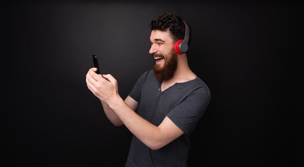 あごひげを生やし、音楽を聴き、孤立した背景の上で電話を使用して幸せな男の写真