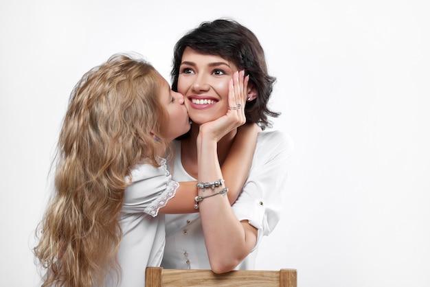 彼女にキスをする娘と幸せな母の写真。彼女はとても美しく、笑顔です。子供は非常に心から抱き合ってキスします。彼らは白いtシャツを着ています。