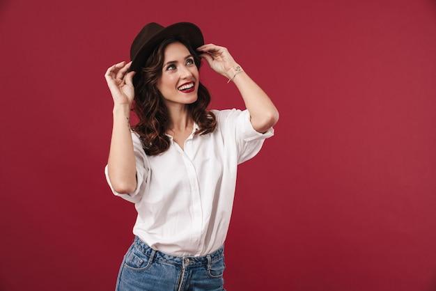 脇を見て赤い壁に孤立してポーズをとって幸せな前向きな笑顔の若い驚くべき女性の写真。