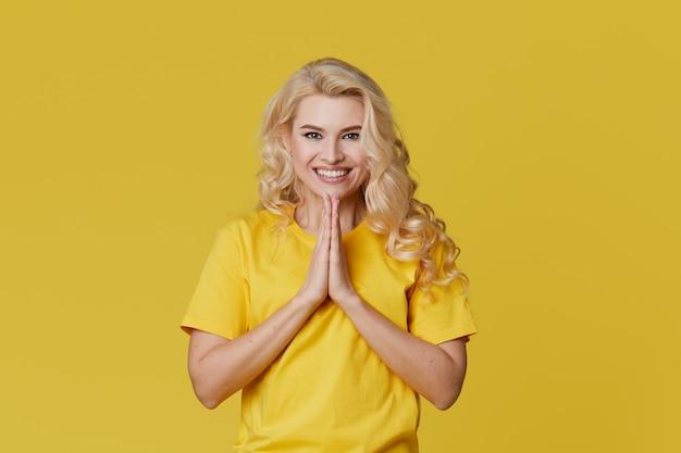 Фото счастливой молодой блондинкой, стоящей над желтой стеной