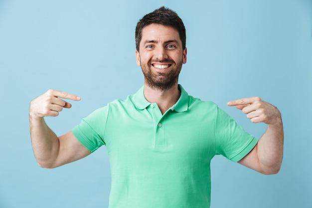 Фото счастливого молодого красивого бородатого мужчины, позирующего изолированным над синим указанием стены.