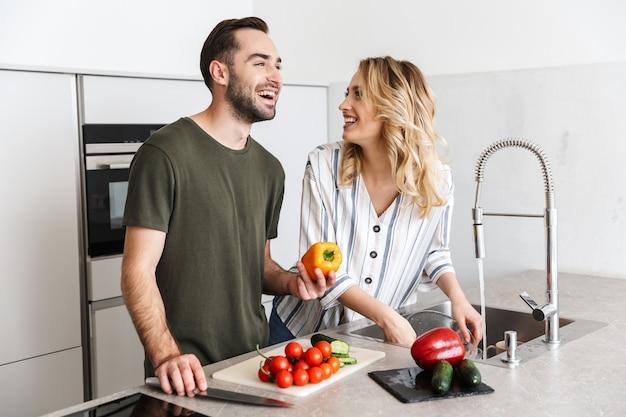 野菜サラダを調理するキッチンで屋内で幸せな若い愛情のあるカップルの写真は朝食をとります。