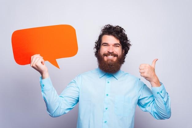 Фотография счастливого молодого человека, держащего оранжевый пустой речевой пузырь и большой палец вверх