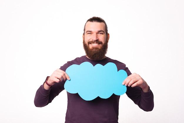 Фотография радостного молодого бородатого мужчины улыбается и держит речевой пузырь в форме облака