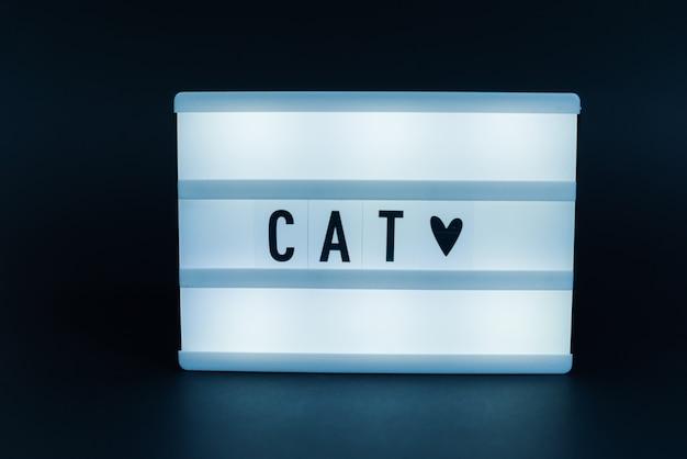 Фото светового короба с текстом, cat, на изолированной темной стене