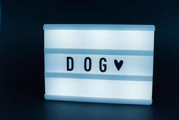 Фото светового короба с текстом, собака, над изолированной темной стеной