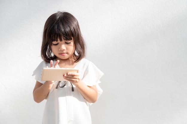 白い背景で隔離の携帯電話を使用して小さな女の子の写真